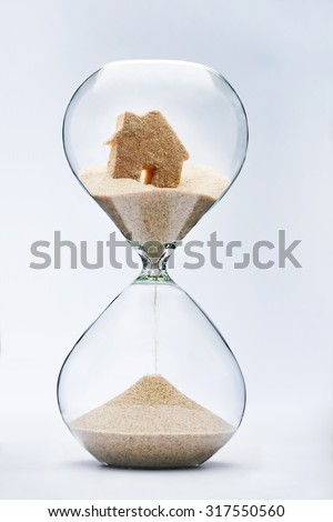 Hourglass house mortgage concept. House flowing down in the hourglass - stock photo