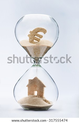 Hourglass house mortgage concept. House made out of falling sand from euro sign flowing through hourglass - stock photo