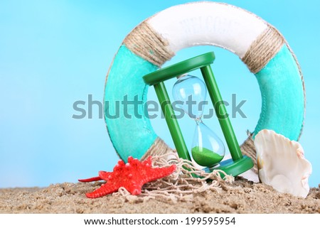Hourglass in sand on blue sky background - stock photo