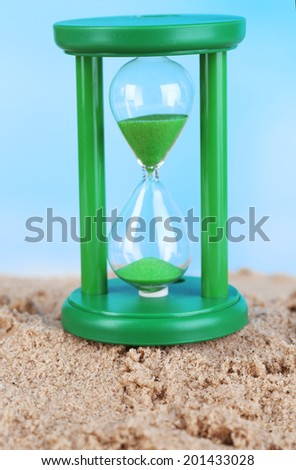 Hourglass in sand on blue sky background