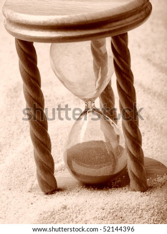 Hourglass in sand, shallow depth of field - stock photo