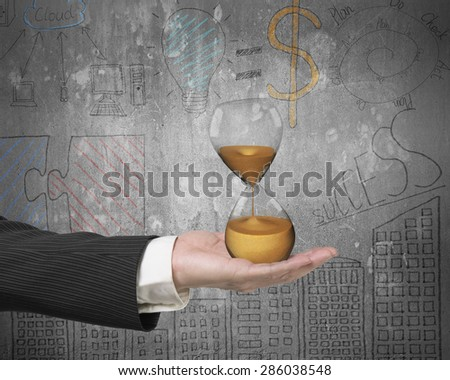 Hourglass in the businessman's hand, with business concepts doodles wall background - stock photo