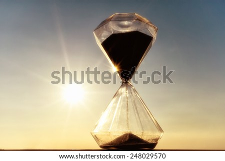 hourglass on a background sunset - stock photo