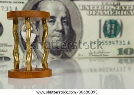 hourglass on big dollar background - stock photo