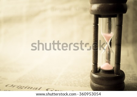 hourglass on newspaper in vintage style