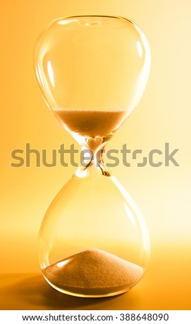 Hourglass on yellow background - stock photo