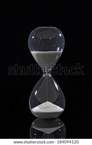 Hourglass - sands of time falling down - stock photo