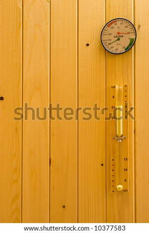 Hourglass, thermometer and hydrometer on wooden wall in sauna. - stock photo