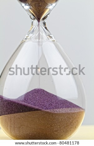 Hourglass ticking away the seconds of the day - stock photo