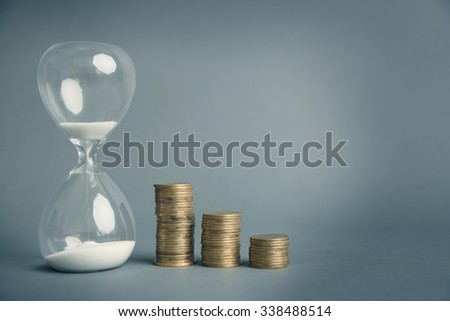 Hourglass with coins on gray background - stock photo