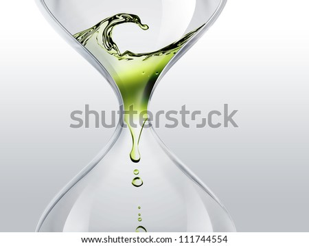 hourglass with green dripping water close-up - stock photo