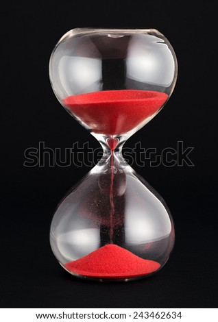 Hourglass with red sand running through the glass bulbs counting down the remaining time as it measures the passing minutes or hours, on a black background - stock photo
