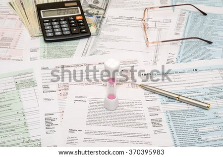 Hourglass with tax form 1040, calculator, pen and dollar bills