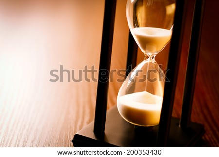 Hourglass with the sand running through in a wood frame on a wooden surface with shine and copyspace - stock photo