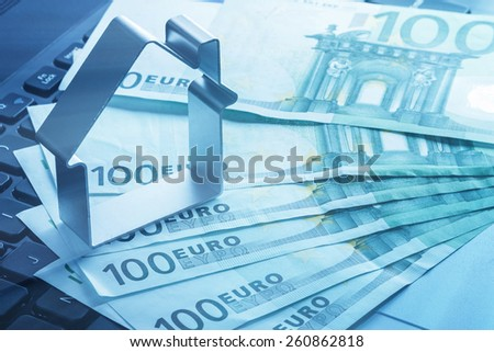House and euro banknotes over laptop keyboard - stock photo