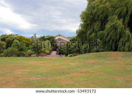 House and foot bridge among trees - stock photo