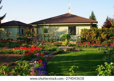 House and Garden displaying annual and perennial gardens in full bloom.