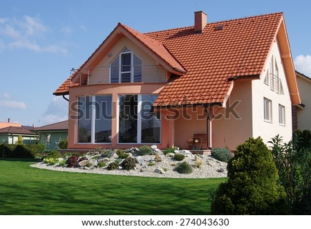 House and Garden displaying annual and perennial gardens in full bloom. - stock photo