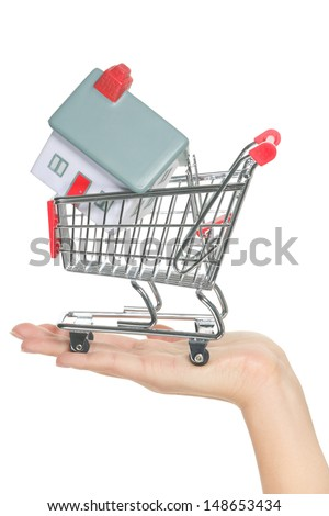 House and home for sale in shopping cart concept. Hand showing mini model house in miniature shopping cart. Buying new house, real estate and home mortgage conceptual image isolated, white background. - stock photo