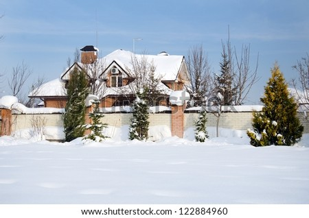 house and its garden under snow - stock photo