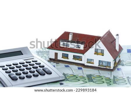 house and money with calculator and white background