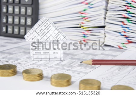 House and pencil on finance account have blur pile of gold coins with calculator place vertical and pile overload paperwork of report and receipt with colorful paperclip as foreground and background.