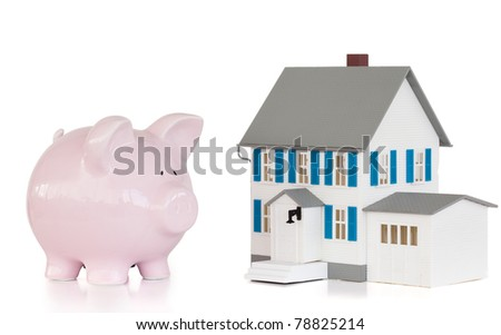 House and pink piggy bank against a white background