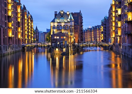 House and two brides illuminated at evening in old warehouse district (Speicherstadt), Hamburg, Germany - stock photo