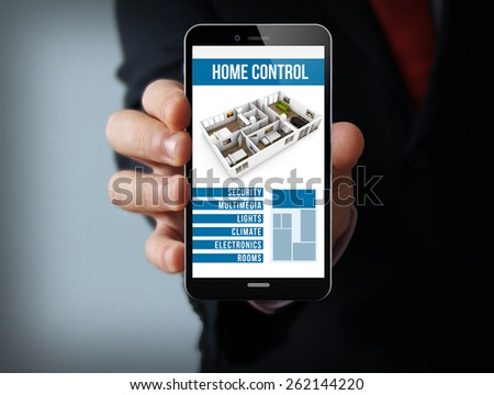 house automation concept: businessman hand holding a touch phone with smart home control application on the screen  - stock photo