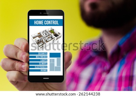 house automation concept: Hipster with beard and checked shirt showing smart home remote control on the screen - stock photo
