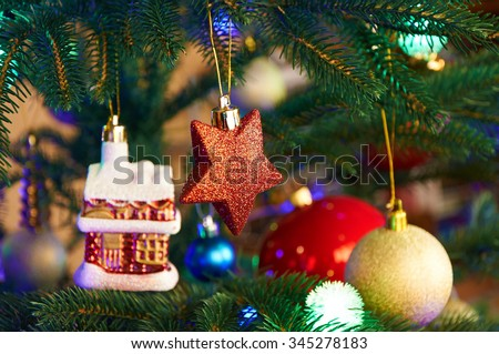 House, balls, stars and lighting garland on the Christmas tree