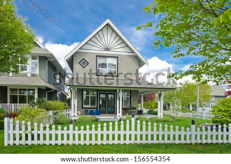 House behind county style wooden fence and nicely trimmed front yard lawn. - stock photo