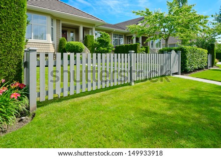 House behind county style wooden fence and nicely trimmed lawn. - stock photo