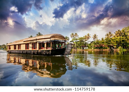 House boat in backwaters near palms at cloudy blue sky in Alappuzha, Kerala, India - stock photo
