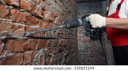 House-builder in uniform and red helmet working with a plugger against the brick wall - stock photo