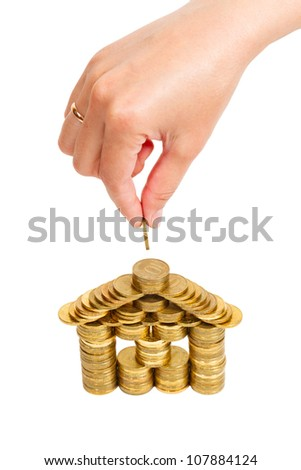 house built of coins female hand isolated on white background - stock photo