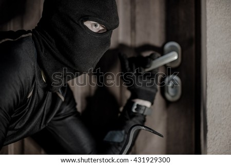 House Burglar in Mask Taking Action. Checking House Doors. House Burglary Concept. - stock photo