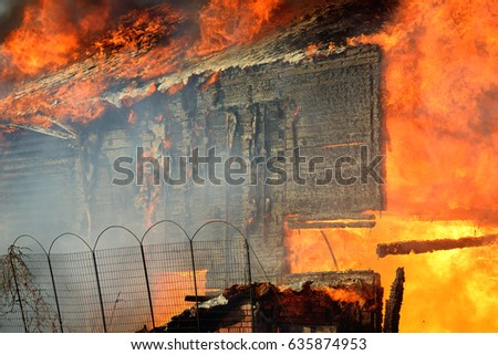 House burning on fire. Building covered by flame. Flaming wooden construction.