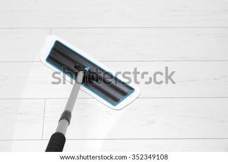 house cleaning - mop washing white laminate floor - stock photo