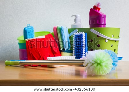 House cleaning set on wooden table over wall background