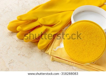 House cleaning tools -  rubber gloves, cleaning cloth, sponge and house cleaning cream on marble.