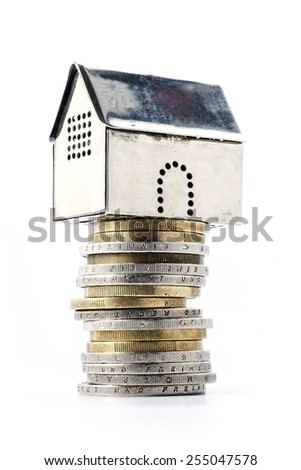 house construction with reliable financing or profit by real estate investment, metallic model house on a pile of coins, isolated on white background, concept image - stock photo