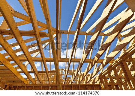 House construction with wood framing and roof trusses against a blue sky for your dream home. - stock photo