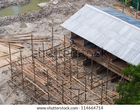 house construction work with worker nailing the wooden path - stock photo