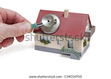 House diagnostics. Model house with hand and stethoscope on white background - stock photo