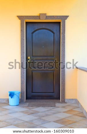 house door and cleaning bucket in the porch - stock photo