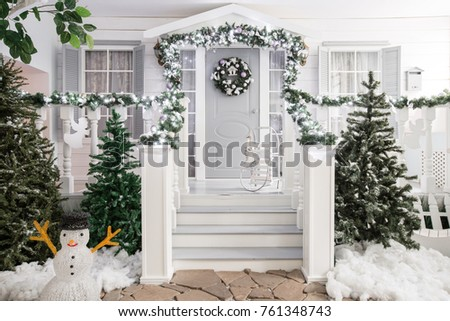house entrance decorated for holidays. Christmas decoration. garland of fir tree branches and lights on the railing