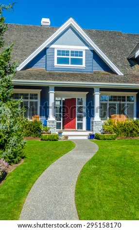 House entrance with doorway and nicely trimmed and landscaped front yard. Vertical. - stock photo