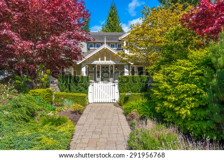 House entrance with nicely paved doorway and trimmed and landscaped front yard. - stock photo
