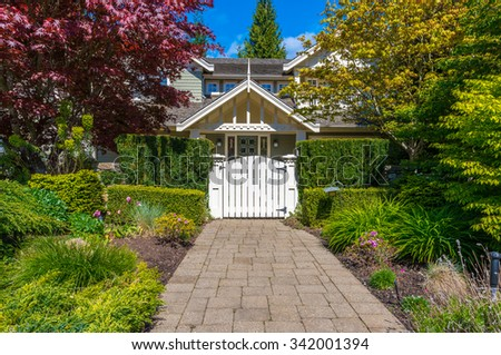 House entrance with nicely trimmed and landscaped front yard and paved doorway.